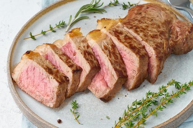 Bistecca di manzo chetogenica di dieta cheto, striploin sul piatto grigio su bianco. ricetta cibo paleo