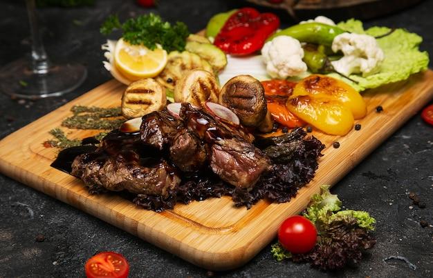 Bistecca di manzo club con salsa al pepe e verdure grigliate sul tagliere