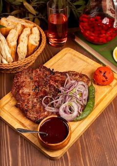 Bistecca di manzo con barbecue, salsa barbecue ed erbe aromatiche, insalata di cipolle, pepe alla griglia e pomodoro sul piatto di legno