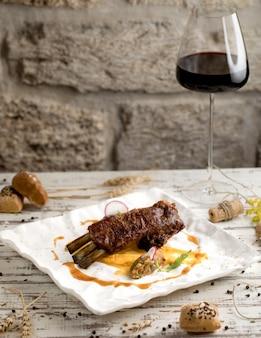Bistecca di manzo con salsa e un bicchiere di vino rosso in un piatto bianco.