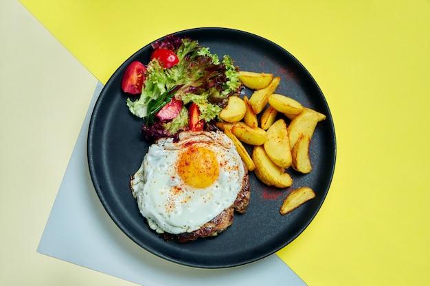 Bistecca di manzo con uova fritte con contorno di insalata e patate fritte su un piatto nero su una superficie colorata alimento appetitoso per pranzo