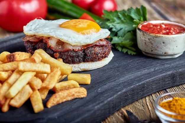 Bistecca di manzo con uovo e insalata di verdure e verdure. sfondo in legno, tavola, cucina raffinata