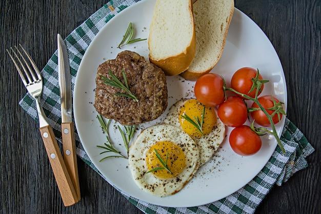 Bistecca di manzo con uovo fritto in spezie. decorato con rosmarino, ciliegia fresca e fette di pane. archiviato su un piatto bianco.