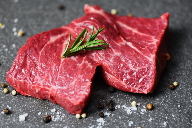 Bistecca di manzo cruda con erbe e spezie - manzo di carne fresca affettato sulla superficie nera