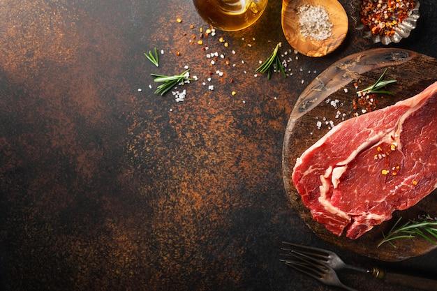 Bistecca di manzo cruda con ingredienti sul tavolo