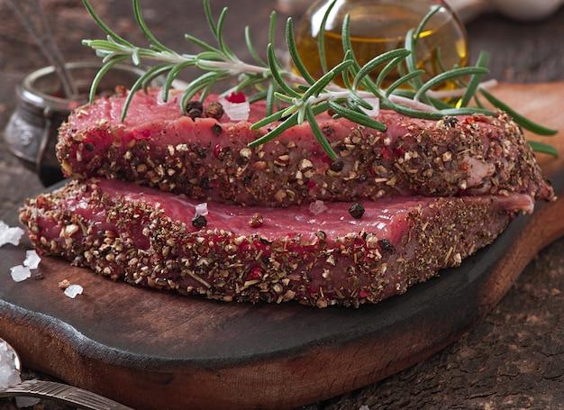 Bistecca di manzo cruda con spezie e un rametto di rosmarino