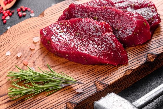 Bistecca di manzo cruda fresca mignon, con sale, grani di pepe, timo, pomodori. carne marmorizzata fresca cruda bistecca e condimenti