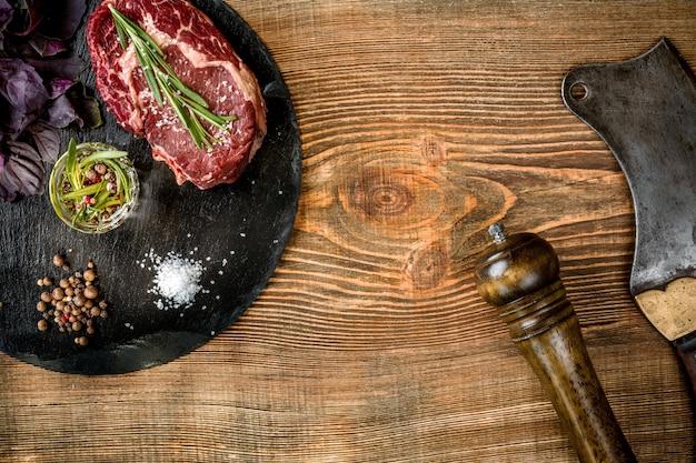 Bistecca di manzo cruda invecchiata secca con ingredienti per grigliare