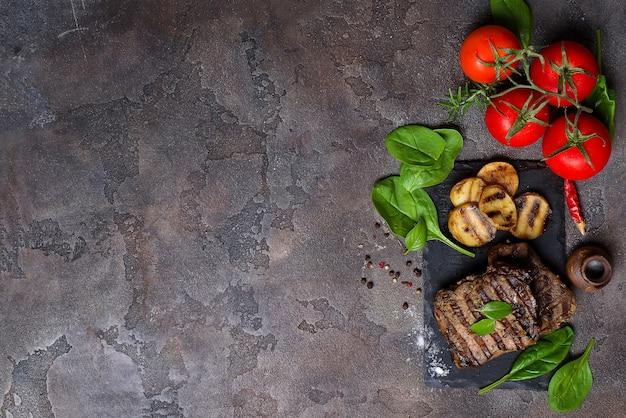 Bistecca di manzo e verdure grigliate sul bordo di ardesia sul tavolo di pietra.
