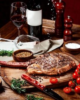 Bistecca di manzo guarnita con sale kosher su tavola di legno