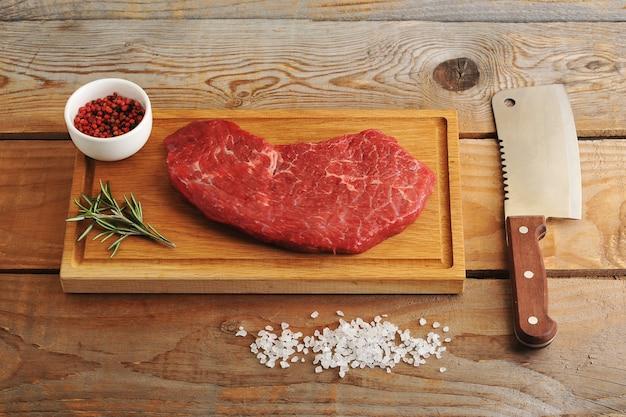 Bistecca di manzo marmorizzata sulla tavola con rosmarino, spezie e un coltello machete