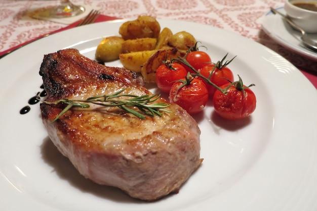 Bistecca di manzo o maiale con pomodoro e patate grigliate sul piatto bianco
