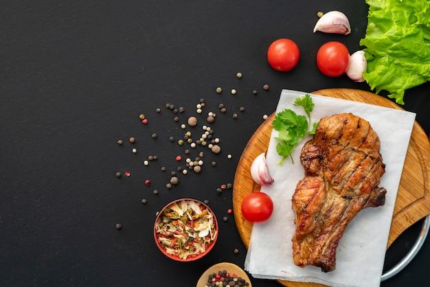 Bistecca di manzo piccante cotta su carbone o carne arrostita, pepe e letucce verdi