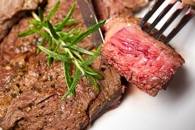 Bistecca di manzo posteriore media. piatto bianco con pezzo di bistecca di manzo sulla forcella.