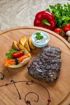 Bistecca di manzo servita con patatine fritte e verdure bollite nel piatto di legno