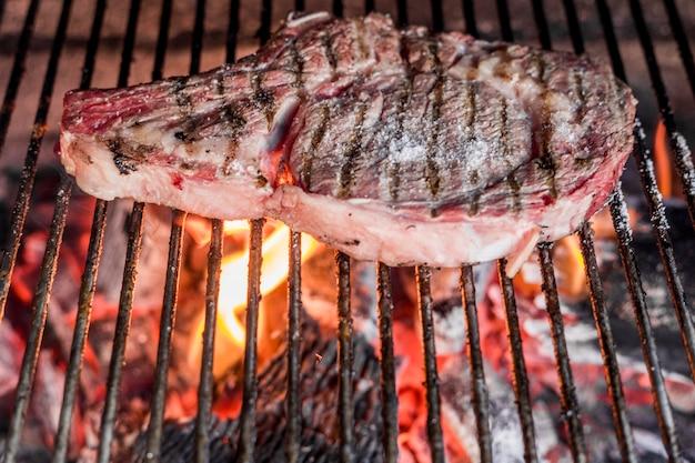 Bistecca di manzo su lamiera di metallo grigliata sopra il carbone in fiamme