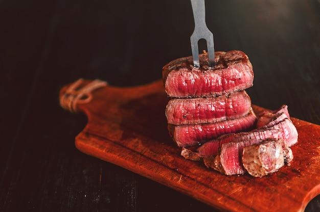 Bistecca di manzo su una forchetta su una superficie di legno scuro