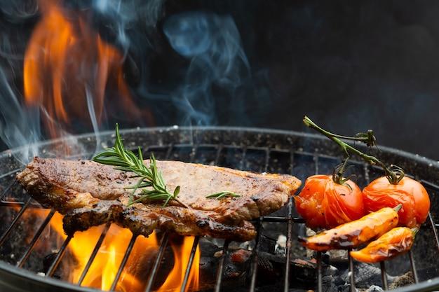 Bistecca di manzo sulla griglia della griglia, fiamme su sfondo con pomodori e sale di rosmarino pepe