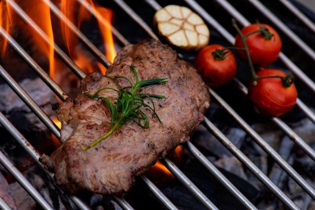 Bistecca di manzo sulla griglia griglia, fiamme su sfondo