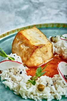 Bistecca di merluzzo con riso e salsa su un piatto blu su uno sfondo di cemento.