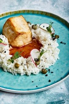 Bistecca di merluzzo con riso e salsa su un piatto blu su uno spazio di cemento.