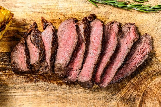 Bistecca di mignon alla griglia affettata su un tagliere di legno. filetto di manzo.
