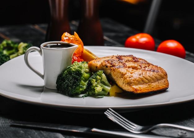 Bistecca di pesce alla griglia vista frontale con broccoli e salsa di melograno