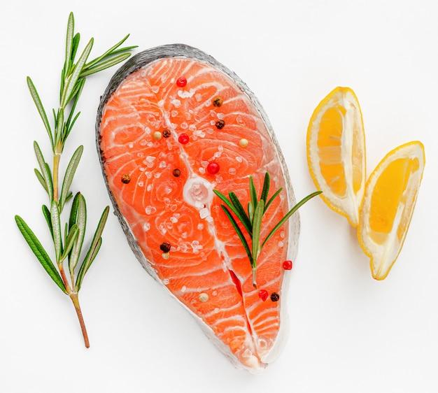Bistecca di pesce salmone fresco con rosmarino e limone piatto lay, concetto di frutti di mare.