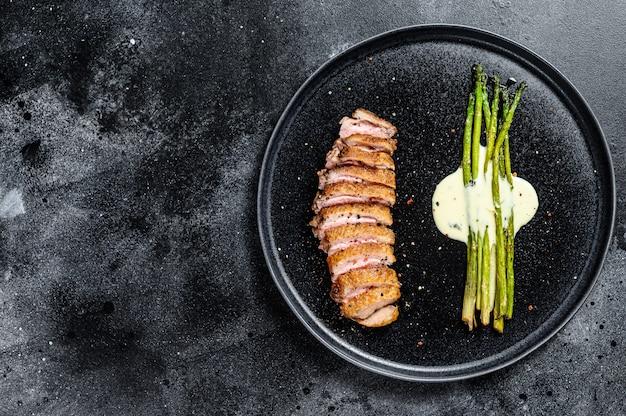 Bistecca di petto d'anatra alla griglia con asparagi al forno. sfondo nero. vista dall'alto. copia spazio