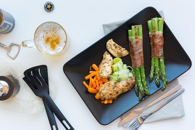 Bistecca di petto di pollo con asparagi avvolti in pancetta