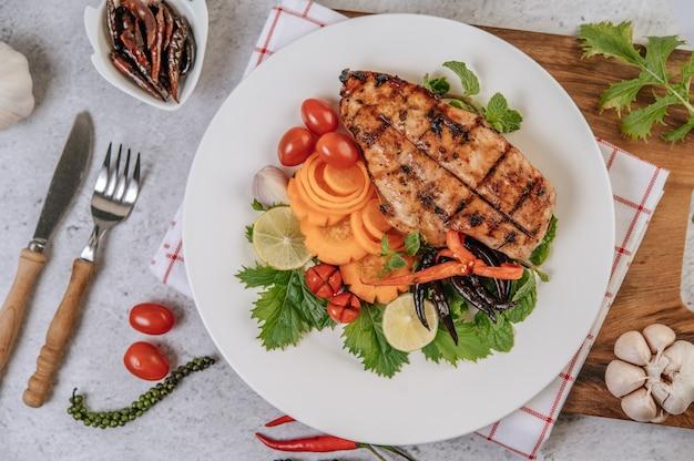 Bistecca di pollo con limone, pomodoro, peperoncino e carota sul piatto bianco.