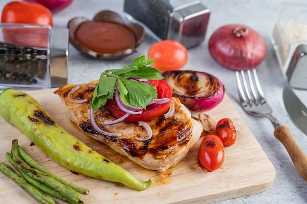 Bistecca di pollo disposta su un vassoio di legno.