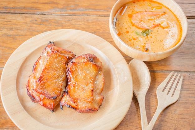 Bistecca di pollo e zuppa piccante sul tavolo di legno