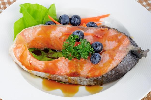 Bistecca di salmone con verdure e frutta.