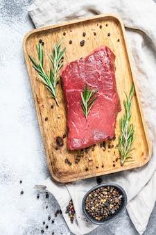Bistecca di striscia cruda di new york su un vassoio di legno. carne di manzo. vista dall'alto