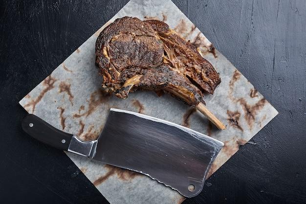 Bistecca di tomahawk con verdure e un coltello sul tavolo. carne alla griglia con verdure grigliate e verdure fresche sul tavolo.