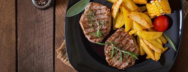 Bistecca di vitello tenera e succosa mediamente rara con patatine fritte