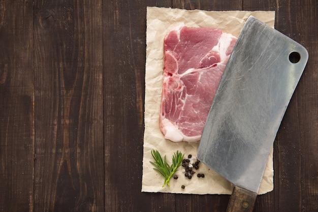 Bistecca e mannaia crude di braciola di maiale su fondo di legno
