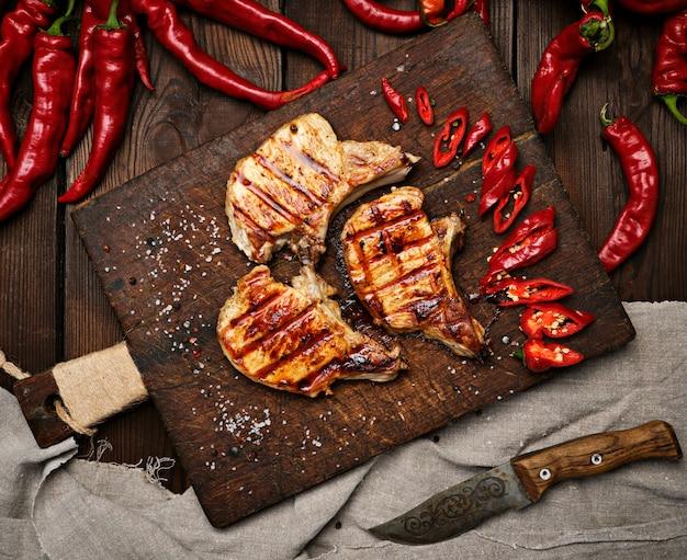 Bistecca fritta di maiale sulla costola si trova su una tavola di legno marrone vintage