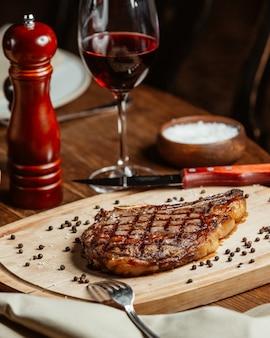 Bistecca ordinata su un supporto di legno con un bicchiere di vino rosso