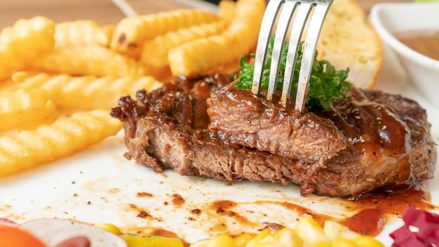 Bistecca, patate fritte e verdure su un piatto bianco.