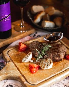 Bistecca servita con aglio grigliato, fette di pomodoro, rametto di rosmarino e salsa