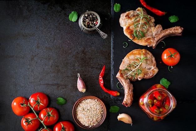 Bistecca succosa arrostita sull'osso con le verdure su un fondo scuro. vista dall'alto