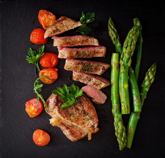 Bistecca succosa mediamente rara di manzo con spezie e pomodori, asparagi. vista dall'alto