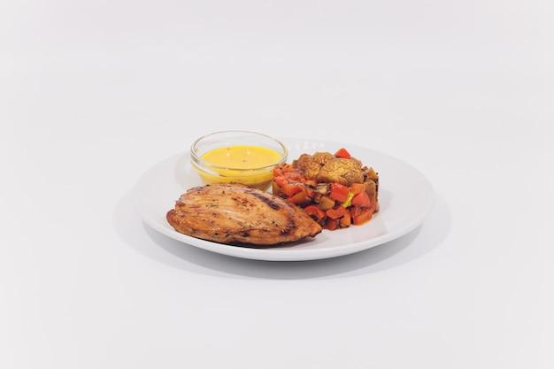 Bistecche alla griglia, patate lesse e insalata di verdure su sfondo bianco.