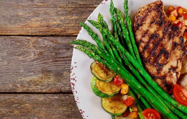 Bistecche alla griglia, patatine e asparagi