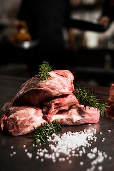 Bistecche di carne cruda con rosmarino sul tavolo