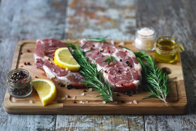 Bistecche di carne cruda su un tagliere. carni fresche con rosmarino e spezie.