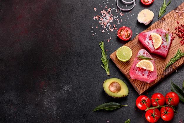 Bistecche di filetto di tonno fresco con spezie ed erbe aromatiche su sfondo nero