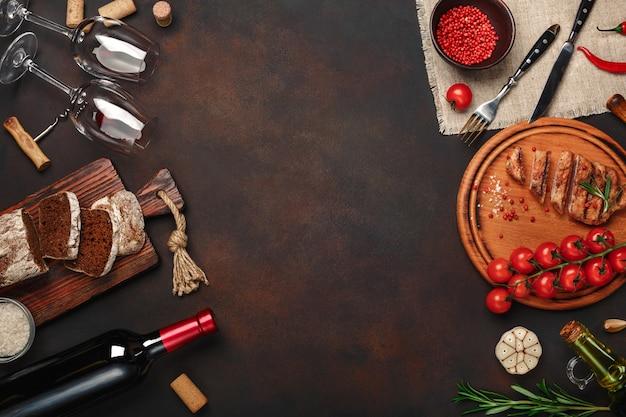 Bistecche di maiale alla griglia a fette con bottiglia di vino, bicchiere di vino, cavatappi, coltello, forchetta, pane nero, pomodorini, aglio, cipolla e rosmarino su sfondo arrugginito